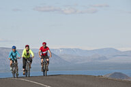 Cyclists on road next to Thingvallavatn, Langjokull in  background, Thingvellir National Park, South West Iceland - CUF36511