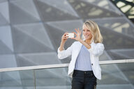 Young businesswoman taking photograph on smartphone outside office building - CUF36523