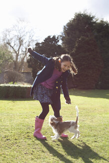 Girl playing in the garden with her pet dog - CUF36658