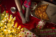 Young woman's legs amongst christmas gifts and pizza box - ISF14444