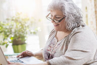 Mature woman at home using laptop - ISF14483