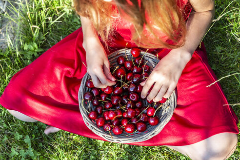 Girl with basket of cherries sitting on a meadow, partial view - SARF03813