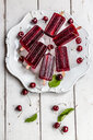 Homemade cherry ice lollies, ice cubes and cherries on plate - SARF03822