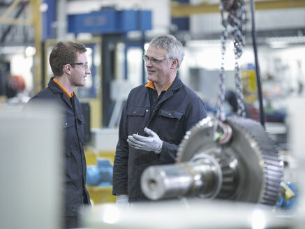 Engineer and apprentice in discussion next to gear wheel at work station in factory - CUF36726