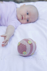 Baby girl reaching for ball - CUF36774