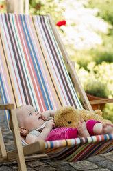 Baby girl sitting on deck chair with teddy bear - CUF36777
