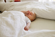 Baby girl asleep on bed - CUF36783