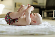 Baby girl lying on back playing with feet - CUF36792