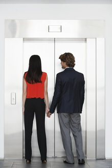 Work colleagues holding hands in front of elevator - CUF36816