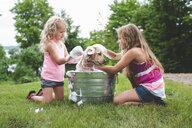 Two sisters bathing pet Labrador Retriever puppy - CUF36864