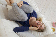 Woman lying on sofa laughing on smartphone - CUF36876