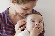Mother nuzzling baby boy on head - CUF36882