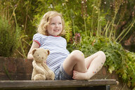Girl on garden seat with teddy bear and star stickers on legs - CUF36906