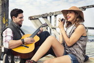 Young couple playing acoustic guitar on old pier, Cape Town, Western Cape, South Africa - CUF36927