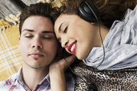 Overhead view of young couple listening to headphones with eyes closed on pier - CUF36930