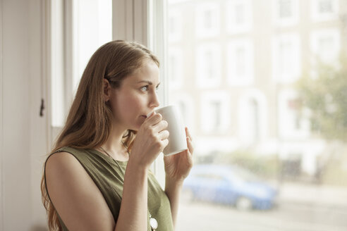 Young woman drinking coffee and gazing through sitting room window - CUF36933