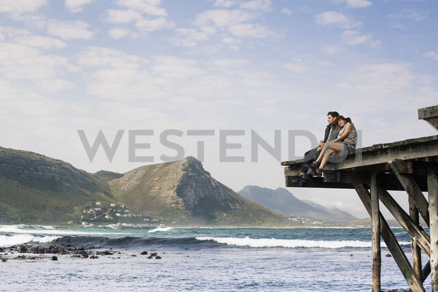 Young couple sitting on edge of old pier, Cape Town, Western Cape, South Africa - CUF36948