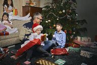 Father on sitting room floor opening christmas gifts with children - CUF36951