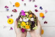Woman's hands holding bowl of salad with edible flowers - SKCF00521