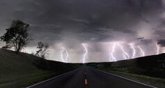 A composite image from 5 images of  cloud-to-ground lightening bolts at the end of a rural road, Lexington, Nebraska, USA - CUF36957
