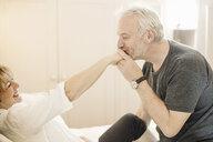 Senior man kissing mature woman's hand - CUF37053