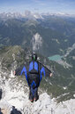 Mid adult man BASE jumping from mountain edge, Alleghe, Dolomites, Italy - CUF37062