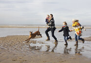Mid adult parents with son, daughter and dog running on beach, Bloemendaal aan Zee, Netherlands - CUF37122