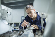 Female engineer turning valves on factory industrial piping - CUF37188
