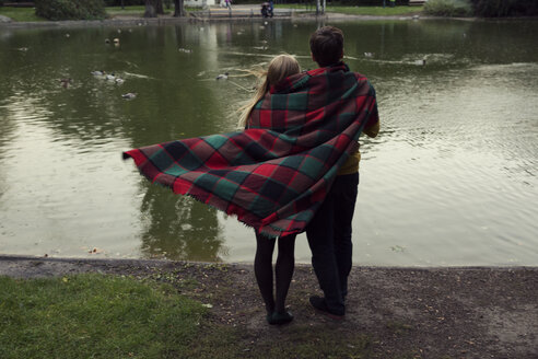 Rear view of young couple wrapped in blanket on park lakeside - CUF37326