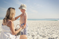 Mid adult mother applying sun lotion to young son on beach, Cape Town, Western Cape, South Africa - CUF37338