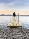 Mid adult man standing on jetty, looking out across water, Thingvellir, Iceland - CUF37374