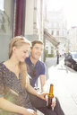 Young couple at sidewalk cafe drinking beer - CUF37383