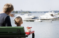 Rear view of male toddler and father watching boats in harbor, Somerniemi, Finland - CUF37437