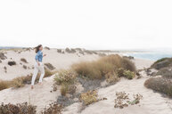 Mid adult woman running up sand dunes, Sardinia, Italy - CUF37443