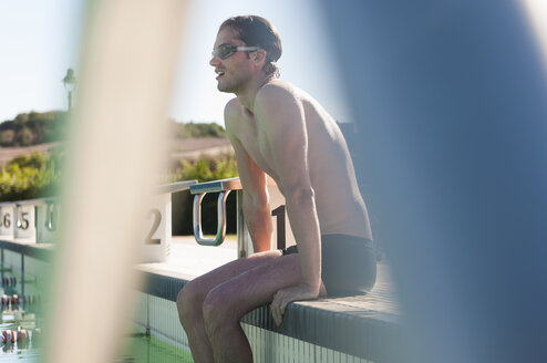 Mid adult male swimmer sitting on side of swimming pool, Sardinia, Italy - CUF37446