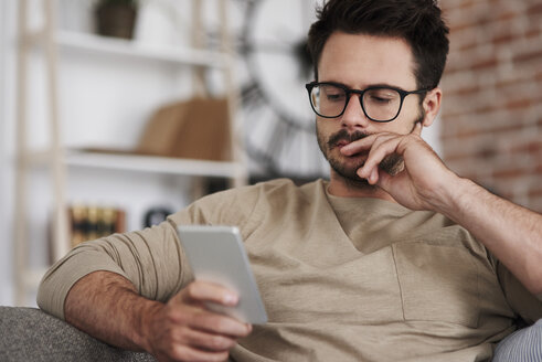 Portrait of man sitting on couch at home looking at smartphone - ABIF00653