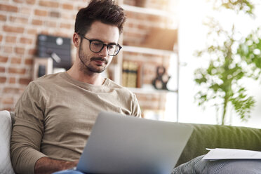 Portrait of man sitting on couch at home using laptop - ABIF00656