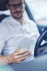 Hand of businessman sitting in car holding cell phone - ABIF00668