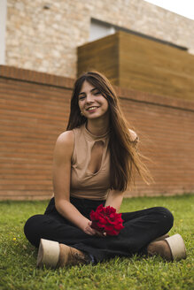 Portrait of smiling young woman with red rose sitting on lawn - ACPF00062