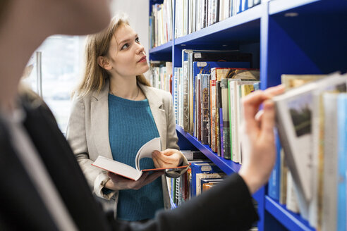 Teenage girl choosing books in a public library - WPEF00497