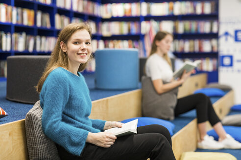 Portrait of smiling teenage girl sitting in public library reading book - WPEF00509