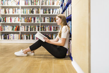 Teenage girl sitting on the floor in a public library reading book - WPEF00515