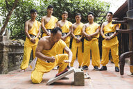 Vietnam, Hanoi, men exercising kung fu, man on flagstone - WPEF00537