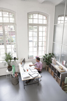 Man working at desk in a loft office - FKF02947