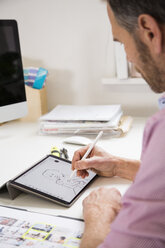 Man working at desk in office drawing female figure on tablet - FKF02971
