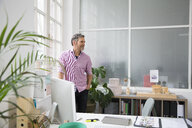 Man standing at the window in a loft office - FKF02977