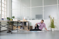 Casual man with plans sitting on the floor in a loft office - FKF02986