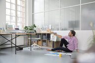Casual man with plans and laptop sitting on the floor in a loft office - FKF02989
