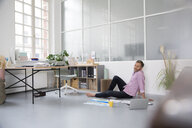 Casual man with plans and laptop sitting on the floor in a loft office - FKF02992