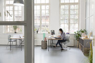 Woman working at desk in a loft office - FKF03007